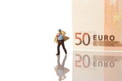 Figurine d'homme d'affaires fonctionnant avec l'euro billet de banque Photographie stock libre de droits