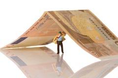Figurine d'homme d'affaires fonctionnant sur un euro billet de banque Photos stock