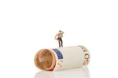 Figurine d'homme d'affaires fonctionnant sur un euro billet de banque Photos libres de droits