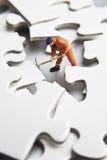 Figurine d'ouvrier sur des parties de puzzle images libres de droits