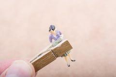 Figurine de femme emprisonnée dans une pince à linge Images stock