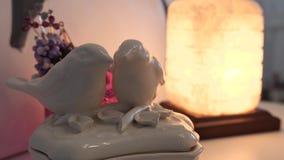 Figurine de porcelaine sous forme de deux oiseaux aimants se tenant sur l'étagère dans la perspective de la lampe dans la maison banque de vidéos