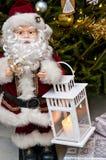 Figurine de Santa Claus avec le bougeoir à l'arbre de Noël Photos stock