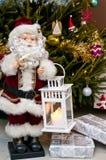Figurine de Santa Claus avec le bougeoir à l'arbre de Noël Photo stock