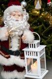 Figurine de Santa Claus avec le bougeoir à l'arbre de Noël Photographie stock