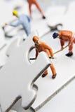 Figurine dell'operaio sulle parti di puzzle Fotografia Stock Libera da Diritti