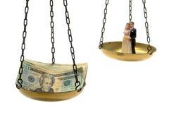 Figurine dos pares do casamento e pilha de dinheiro na escala Fotografia de Stock Royalty Free