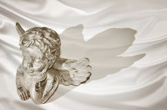 Figurine of a dreaming cherub on silk background Stock Photography