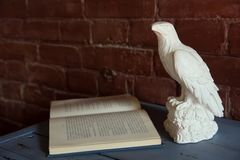 Figurine of an eagle with an open book wooden table Royalty Free Stock Images