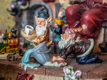 Figurine elves in Santas workshop scrubbing floor. stock photography