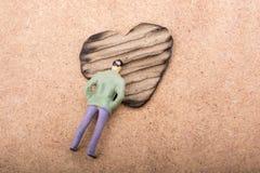 Figurine et en forme de coeur brûlés hors d'un carton Image stock
