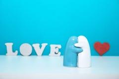 Figurine et lettres d'AMOUR en céramique et coeur rouge Photo stock