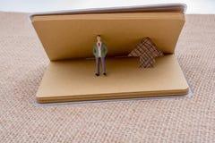 Figurine et une flèche de papier dans un carnet Photographie stock libre de droits