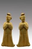 Figurine femminili e fondo grigio di pendenza Fotografia Stock