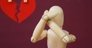 Figurine in front of broken heart. Conceptual image of figurine in front of broken heart 4k stock footage