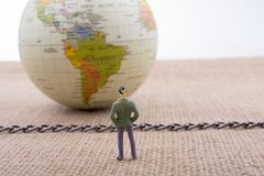 Figurine and Globe with a chain in the middle Royalty Free Stock Images