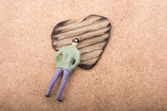 Figurine and Heart shaped burnt out of a cardboard Stock Image