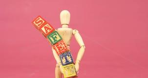Figurine holding alphabet toy block stock video footage