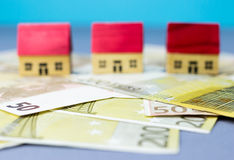 Figurine houses with banknote. Figurine wooden houses on blue background Stock Images