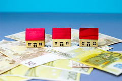 Figurine houses with banknote. Figurine wooden houses on blue background Royalty Free Stock Photography