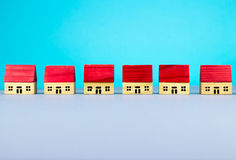 Figurine houses. Figurine wooden houses on blue background Royalty Free Stock Images