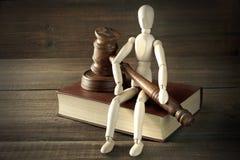 Figurine humaine avec les juges ou le commissaire-priseur Gavel Sit On Book Photos stock