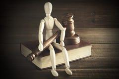 Figurine humaine avec les juges ou le commissaire-priseur Gavel Sit On Book Images libres de droits