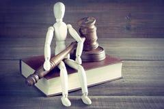 Figurine humaine avec les juges ou le commissaire-priseur Gavel Sit On Book Photographie stock libre de droits