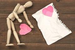 Figurine humanitaire en bois, page de papier déchirée et coeurs brisés Images stock