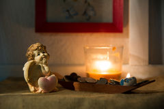 Figurine little angel with a heart who dreams of burning candle Stock Image