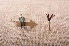 Figurine man led by an arrow on canvas Stock Photo