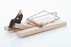 Figurine of man pensioner on mouse trap Royalty Free Stock Photo