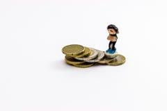 Figurine marchant sur des pièces de monnaie Photos stock