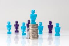 Figurine masculine placée sur la pile des pièces de monnaie avec la figue supplémentaire Photographie stock libre de droits