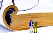 Figurine miniature de couples supérieurs avec le livre et les verres sur le fond Photos libres de droits