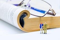 Figurine miniature de couples supérieurs avec le livre et les verres sur le fond Photo stock