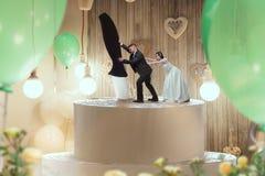 Figurine nuziali del dolce, della sposa e dello sposo sulla cima immagini stock libere da diritti