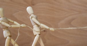 Figurine playing tug-of-war. Conceptual image of figurine playing tug-of-war stock video
