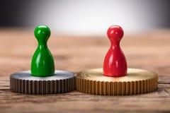 Figurine rosse e verdi del pegno sulle ruote dentate collegate fotografia stock libera da diritti