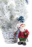 Figurine of Santa Claus with skis in hand next to. Cute Figurine of Santa Claus with skis in hand next to a white Christmas tree Royalty Free Stock Photo