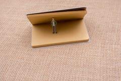 Figurine se tenant dans un carnet Photographie stock libre de droits