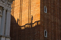 Figurine shadows on a Campanila bell tower wall at piazza San Marco in Venice Royalty Free Stock Photo