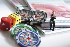Figurine sitting on euro notes with dices and jetons Royalty Free Stock Photos