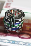Figurine sitting on jetons with euro banknotes, close up Royalty Free Stock Image