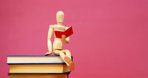 Figurine sitting on stack of book. Against pink background 4k stock video