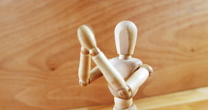 Figurine standing with arms crossed on a wooden floor stock footage