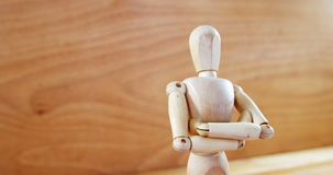 Figurine standing with arms crossed on a wooden floor stock video footage