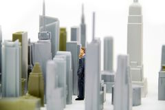 Real Estate Mogul. Figurine standing among city sky scrapers, contemplating a real estate investment Royalty Free Stock Photography