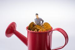 Figurine standing in a watering can full of  fake gold coins royalty free stock photos