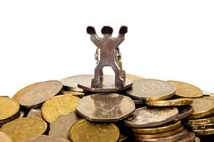 Figurine on top of a pile of coins Royalty Free Stock Photos